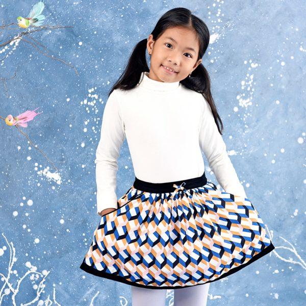 jupe coton crêpe imprimé géométrique bleu roi, rose et jaune moutarde avec une ceinture en velours noir élastique à la taille et deux poches sur les côtés. Collection hiver mode enfant de la marque LA FAUTE A VOLTAIRE