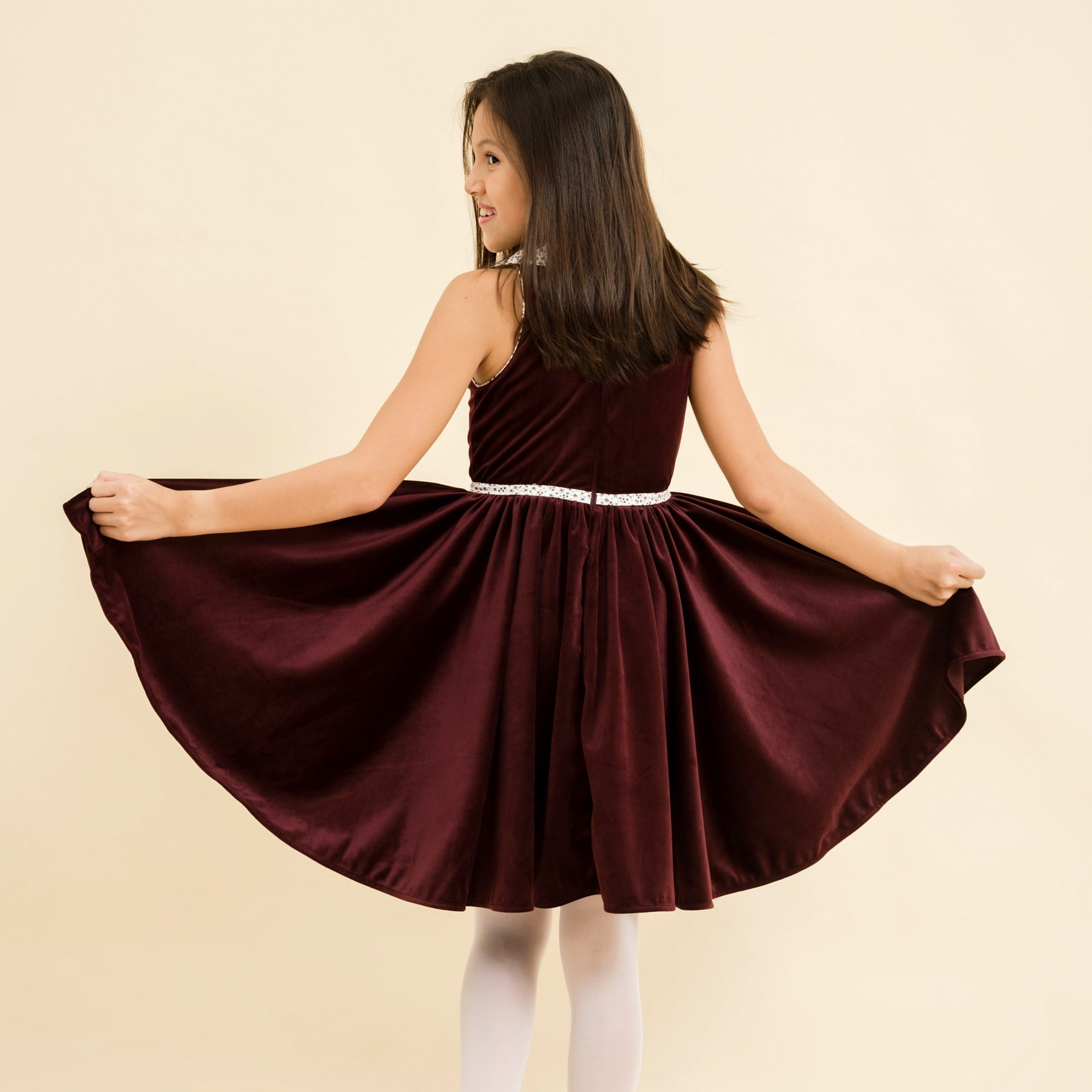 Girl winter twirling sleeveless dress with burgundy velvet fabric and purple liberty floral on the collar and belt. Design by the French retro-chic brand in fair trade LA FAUTE A VOLTAIRE