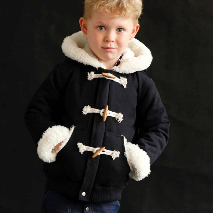 Manteau blouson noir doublé de fausse fourrure toute douce beige à l'intérieur du manteau et de la capuche. Boutons en bois style dufflecoat, poignets retroussables et taille élastique. Mrque créateur pour enfant française LA FAUTE A VOLTAIRE