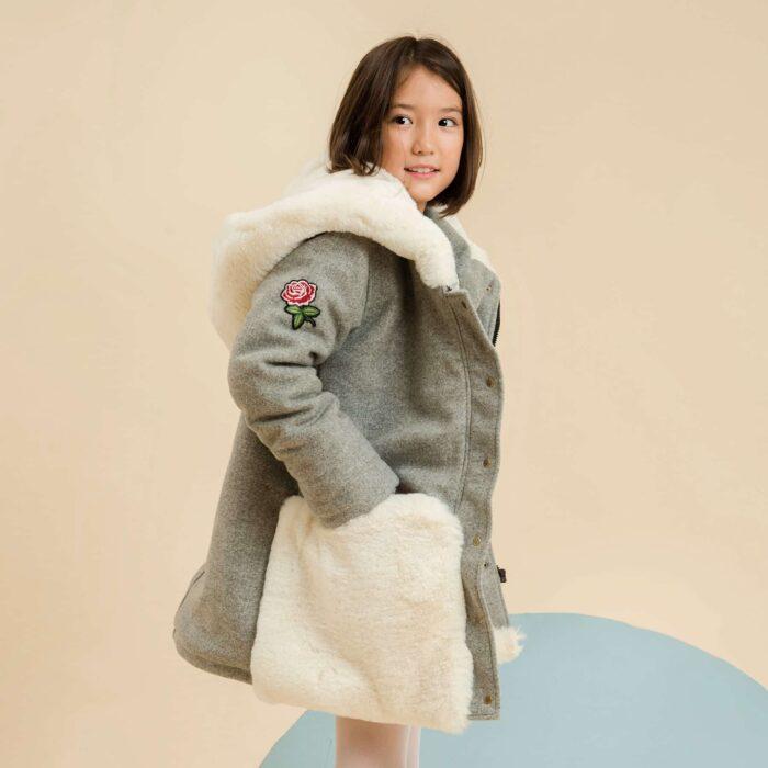 Manteau oversize en laine gris souris, poches et capuches géantes en fausse fourrure blanc cassé, écusson de fleur rose, manche ajustable avec fausse fourrure aux poignets. Marque de mode française en commerce équitable LA FAUTE A VOLTAIRE