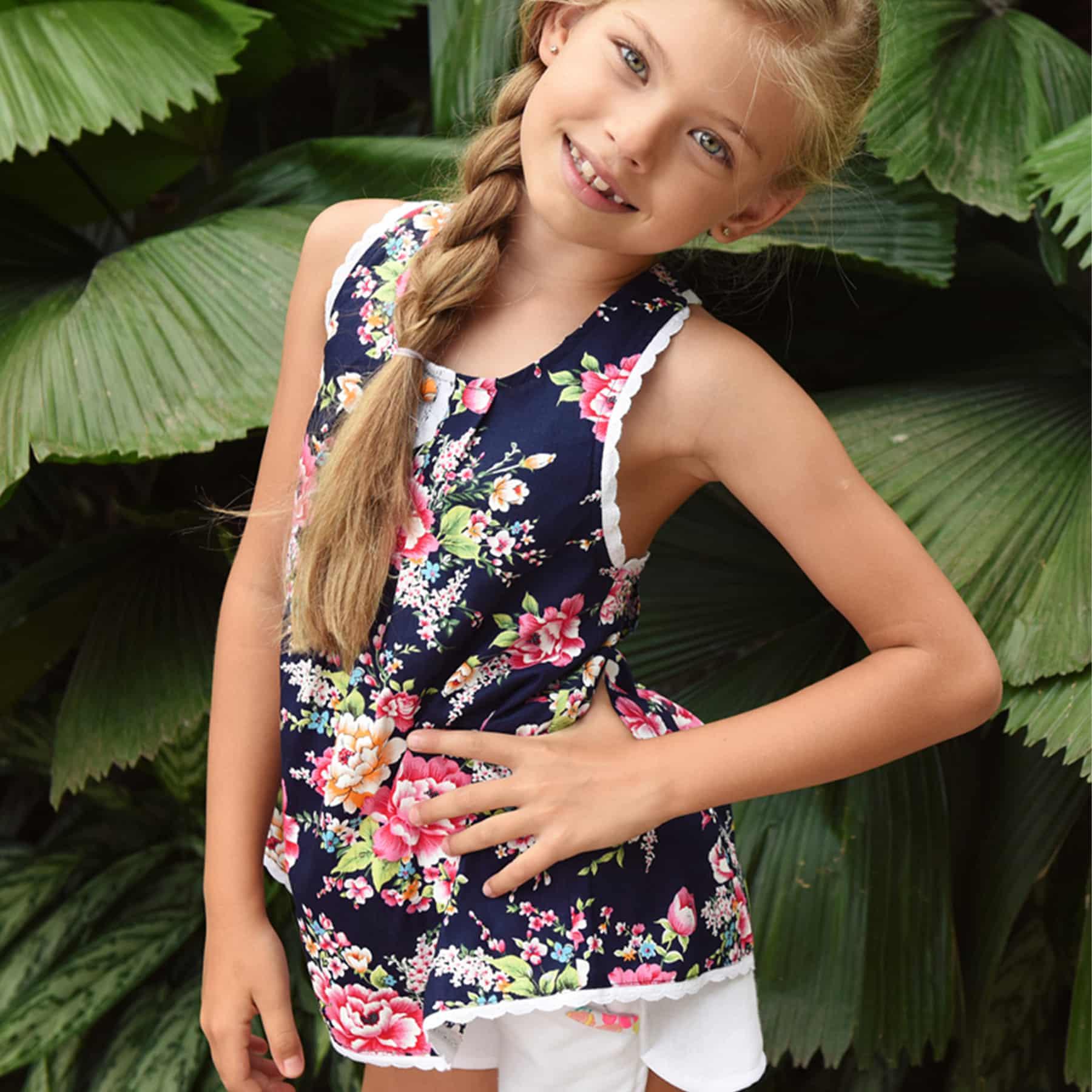 Blouse d'été en coton fleuri liberty bleu marine et rose bordé de fine dentelle blanche avec bretelles croisées dans le dos pour filles de 2 à 14 ans
