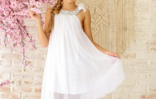 Robe de cérémonie blanche à col arrondie en coton liberty fleuri petites fleurs violette et bretelle fermée par un noeud sur l'épaule en voile blanc. Modèle Alizée de la marque de mode rétro-chic pour enfant en commerce équitable LA FAUTE A VOLTAIRE