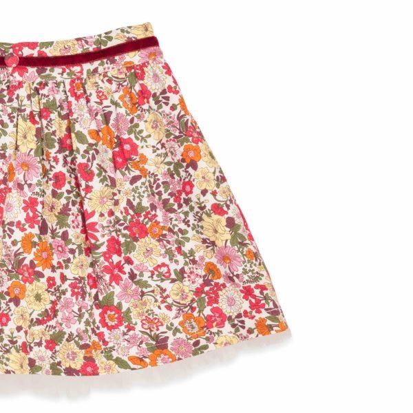 Jupe qui tourne en coton fleuri liberty rouge bordée de tulle blanche avec poches et taille habillée d'une ceinture en velours rouge pour filles de 2 à 14 ans