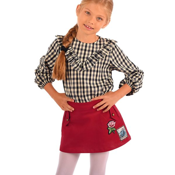 jupe courte en coton bordeaux prune, de forme trapèze, taille ajustable avec élastique dans le dos, écusson d'une fleur rose sur le devant. Vêtement mode enfant de la marque française en commerce équitable de LA FAUTE A VOLTAIRE